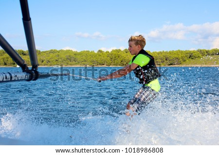 Young sportive teenage boy waterskiing from the boat. Adventurous summer holidays at the sea. Water sport activity on the beach. #1018986808