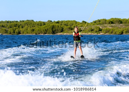 Young sportive teenage boy waterskiing from the boat. Adventurous summer holidays at the sea. Water sport activity on the beach. #1018986814