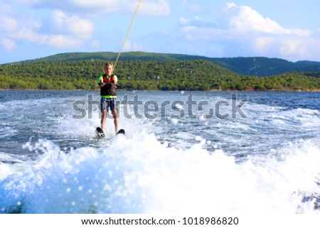 Young sportive teenage boy waterskiing from the boat. Adventurous summer holidays at the sea. Water sport activity on the beach. #1018986820