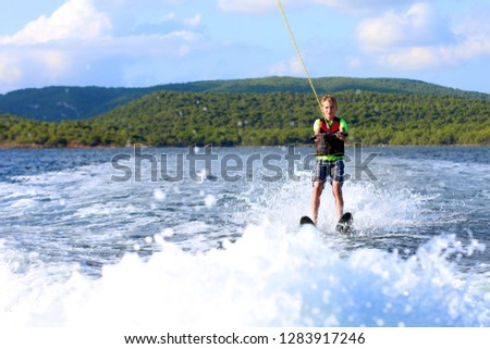 Young sportive teenage boy waterskiing from the boat. Adventurous summer holidays at the sea. Water sport activity on the beach. Sportive family having fun outdoors on a sunny day. #1283917246