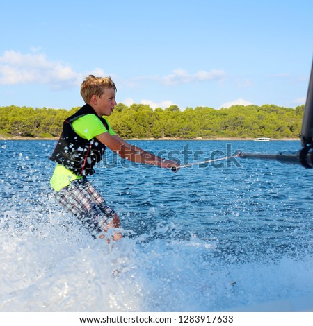 Young sportive teenage boy waterskiing from the boat. Adventurous summer holidays at the sea. Water sport activity on the beach. Sportive family having fun outdoors on a sunny day. #1283917633