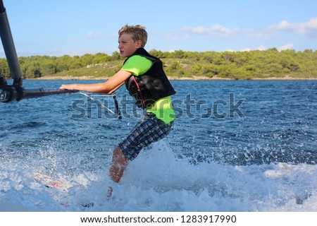 Young sportive teenage boy waterskiing from the boat. Adventurous summer holidays at the sea. Water sport activity on the beach. Sportive family having fun outdoors on a sunny day. #1283917990