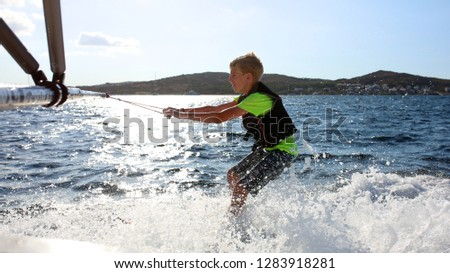 Young sportive teenage boy waterskiing from the boat. Adventurous summer holidays at the sea. Water sport activity on the beach. Sportive family having fun outdoors on a sunny day. #1283918281