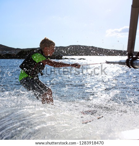 Young sportive teenage boy waterskiing from the boat. Adventurous summer holidays at the sea. Water sport activity on the beach. Sportive family having fun outdoors on a sunny day. #1283918470