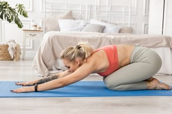 Young sportive woman practicing yoga doing full body exercises, balasana pose, workout, sportswear, gray pants and top, full length indoors, white yoga studio. The girl is worried about her figure.
