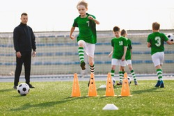 Young sports boys in green sportswear running and jumping over training obstacles on pitch. Soccer youth team playing football training in the summer. Sports activities for kids. Coach with school boy