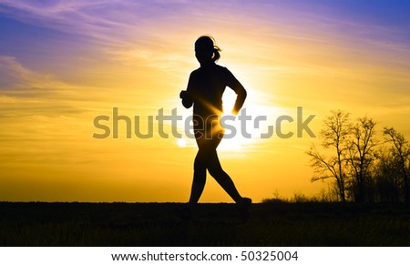 Young sports girl runs in the sunset. - stock photo