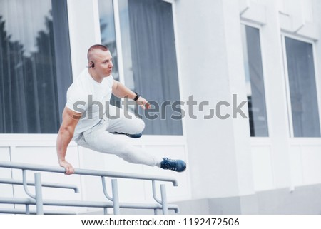 Young sports man doing parkour in the city. #1192472506