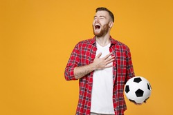 Young sports man football fan in basic red shirt cheer up support favorite team with soccer ball put hand on heart sing anthem isolated on yellow background studio. Tattoo translation life is fight