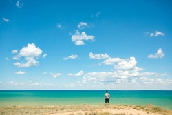 Young sports man leading a healthy lifestyle walks by the sea. Beautiful sky with clouds and sea view