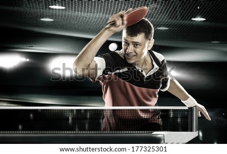 Young Sports Man Tennis-Player In Play On Black Background With Lights