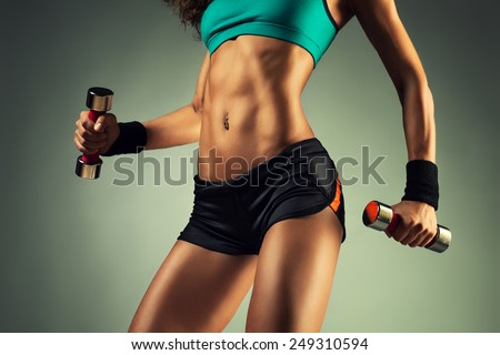 Young sports sexy fitness woman body with dumbbells posing on wall background.