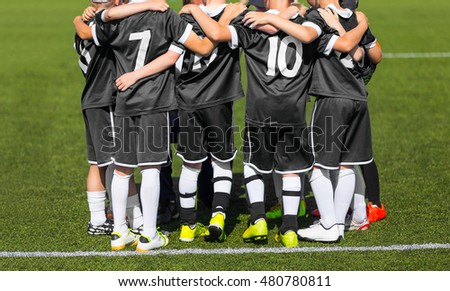 Young sports team. The sport football team with coach; Group photo; Kids with soccer coach gathering before match. Youth soccer football team.