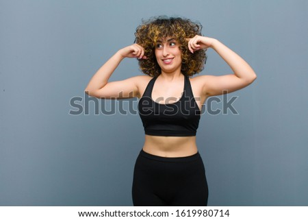 young sports woman feeling confused or doubting, concentrating on an idea, thinking hard, looking to copy space on side against gray wall