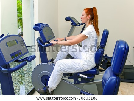 Young sports woman in sport center on velosimulator