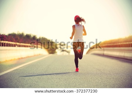 young sports woman runner running on city road #372377230