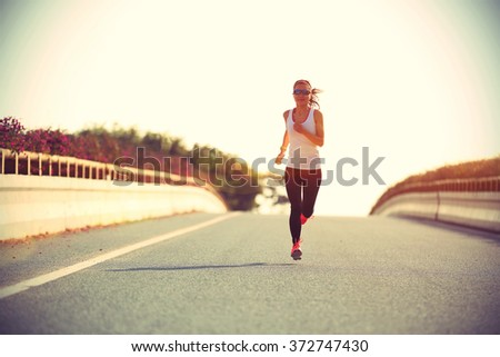 young sports woman runner running on city road #372747430