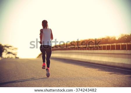 young sports woman runner running on city road #374243482