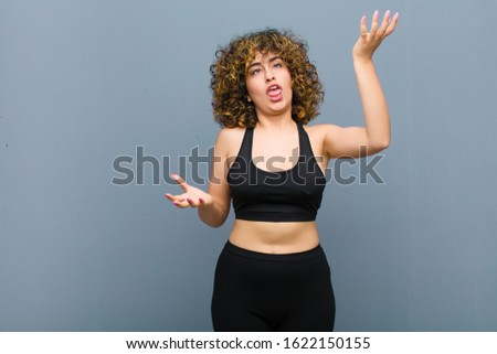 young sports woman shrugging with a dumb, crazy, confused, puzzled expression, feeling annoyed and clueless against gray wall