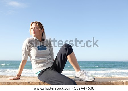 Young sports woman sitting by a beach, taking a break from exercising and being thoughtful against a blue sky.