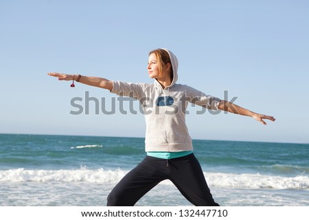 Young sports woman stretching her arms and legs while exercising on a beach during a sunny morning with a blue sky and the sea in the background.