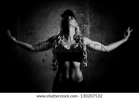 Young sports woman with heavy chain. Black and white.