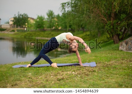 Young sports yoga, practicing yoga, doing wild things, exercise Flip-the-Dog, pose Camatkarasana, training in sportswear in the summer on the lawn against the background of the river. #1454894639