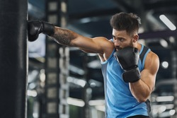 Young sportsman boxing workout at gym, guy punching boxing bag, free space