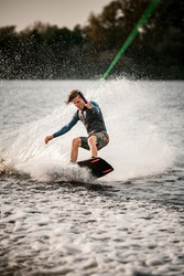 young sportsman in vest stands with bent knees on wakeboard and ride down on the splashing wave.