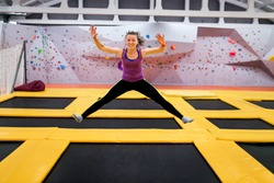 Young sportsman jumping on a trampoline and doing split indoors