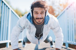 Young sportsman listening to music while doing push ups outdoors, fitness and exercising in the park. Fitness, sport, lifestyle concept