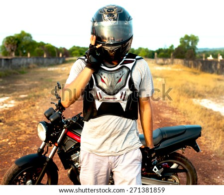 Young sportsman posing on helmet opposite the sunset.Crossing and motorcycle sport style.