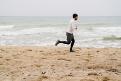 Young sportsman running at the beach, wearing warm clothes, workout