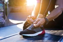 Young sportsman tying shoelaces on sport shoes. Fit, fitness, exercise, workout and healthy lifestyle concept.
