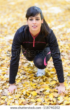 Young sportswoman in starting pose for running.  Ready with hands on ground with golden autumn leaves.