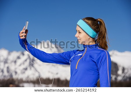 Young sportswoman jogging outside in sunny winter mountains taking selfie.