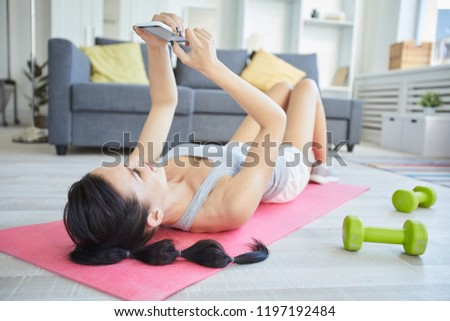 Young sportswoman lying on mat and messaging in smartphone while enjoying break between workouts #1197192484