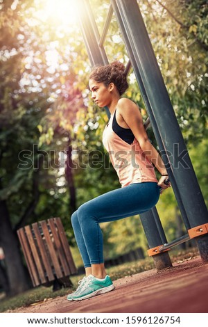 Young sportswoman outdoors at urban setting, exercise training in public park on outdoor gym equipment