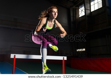Young sportswoman running and jumping over a hurdle. Sprint race with hurdles athletics training concept background