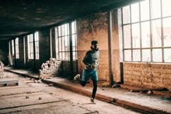 Young sporty african american guy in sportswear and with earphones running in old brick factory.