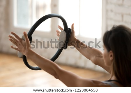 Young sporty attractive woman doing pilates toning exercise for arms and shoulders with ring, fitness with pilates magic circle in hands, working out, indoor close up. Strength, well being concept