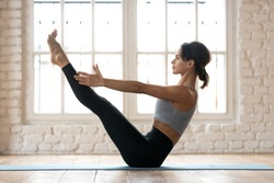 Young sporty attractive woman practicing yoga, doing Paripurna Navasana exercise, balance pose, working out, wearing sportswear, black pants and top, indoor full length, white yoga studio