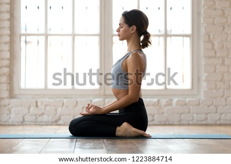 Photo of Young sporty attractive woman practicing yoga, doing seiza exercise, vajrasana pose, working out, wearing sportswear, pants and top, indoor full length, white yoga studio