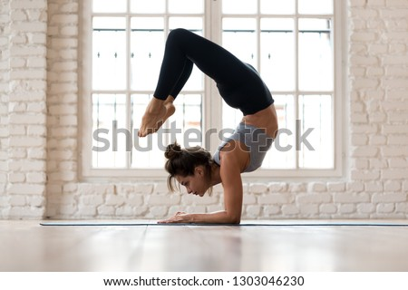 Young sporty attractive woman practicing yoga, doing Vrischikasana, Scorpion exercise, handstand pose, working out, wearing sportswear, black pants and top, indoor full length, yoga studio