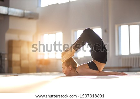Young sporty attractive woman practicing yoga, stretching in scorpion excercise, working out, wearing sportswear, black pants, bra, full length, indoor shot