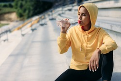 Young sporty brunette dressed in yellow hoodie and black leggings sitting on stairs and drinking fresh water. Active woman having break during outdoors training.