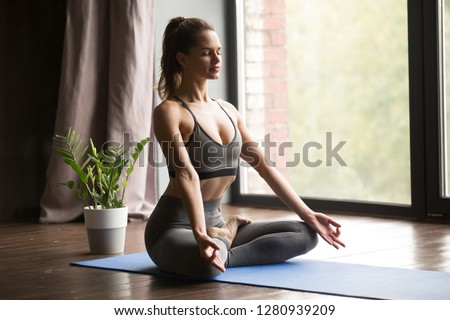 Young sporty calm attractive woman practicing yoga, doing Ardha Padmasana exercise, Half Lotus pose with mudra, working out, wearing sportswear, grey pants and top, indoor full length, yoga studio