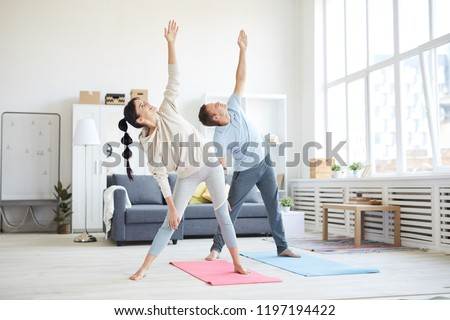 Young sporty couple in activewear raising their left arms while exercising in living-room at home