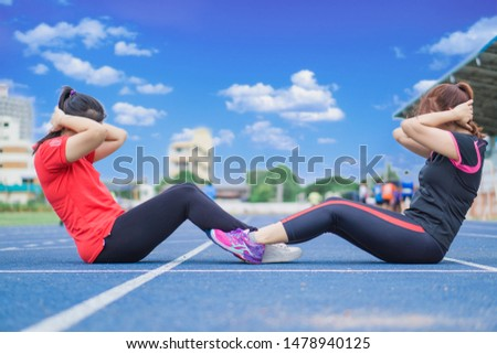Young sporty couple women working out together at running track. Young sporty couple women sit-ups to together on running track before running. Sport and exercise concept.
