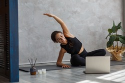 Young sporty female yoga instructor coaching online, making video of yoga lessons on laptop camera. Beautiful woman practicing yoga poses. Yoga postures, meditation, relaxation, wellbeing and health.